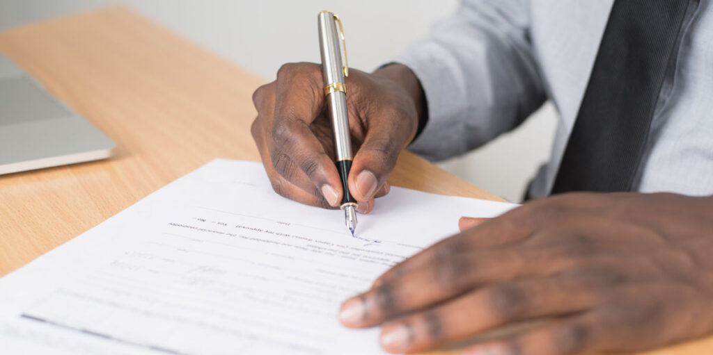 Man with pen signing form